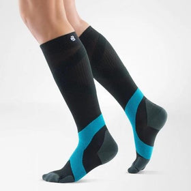 A black and blue colour leg compression sleeves with the logo of Bauerfeind Australia on it and being worn on both legs. It is considered one of the best sports compression socks for ball and racket.