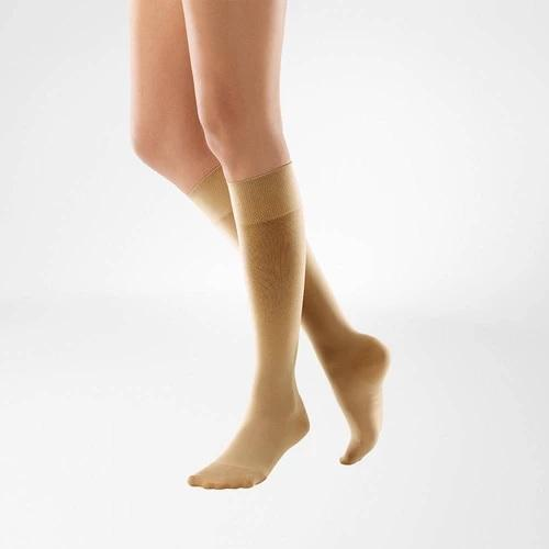 Compression stockings in caramel colour and is worn on both legs. It is considered as one of Bauerfeind Australia's best recovery supports and braces, the VenoTrain Knee High Compression Stockings (Caramel).