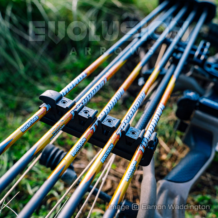Tomahawk .005 arrows by Evolusion Arrows from Ten Zone Archery in a bow quiver of a compound bow lying on green undergrowth. Image copyright Eamon Waddington.