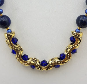 Beautiful Lapis Lazuli Stones surround a Gold Plated ornate curved Tube adorned with Swarovski Crystals. Also includes Swarovski Pearls, Miyuki Delica, Gold Fill, and Gold Plate.