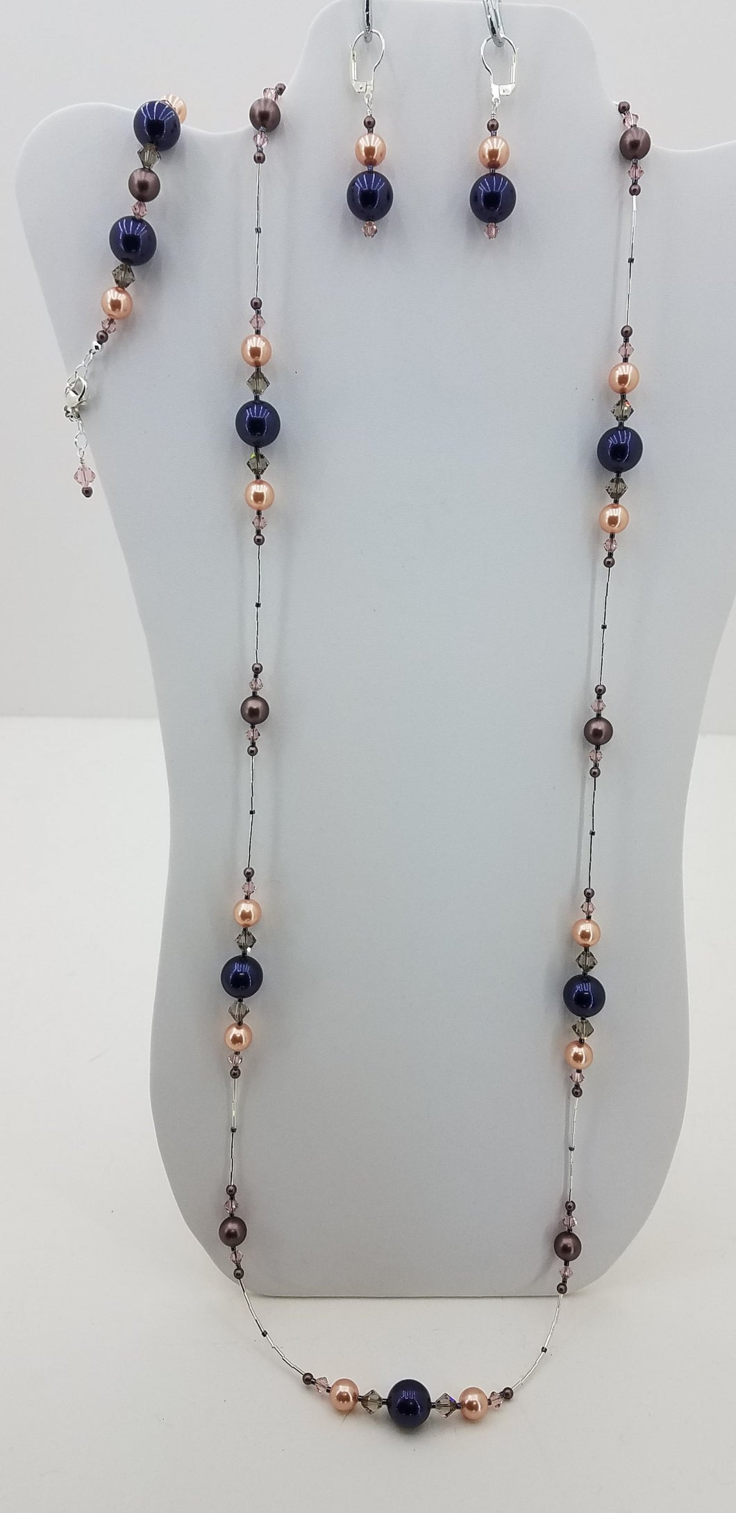 A lightweight and long combination of Crystals & Crystal Pearls in night blue, peach, & brown velvet,  & Sterling Silver necklace, earrings, & bracelet