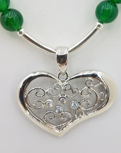A swirly sterling silver heart accented with tiny cubic zirconia hangs from vibrant green onyx, soft erinite crystals, and tiny white crystal pearls.