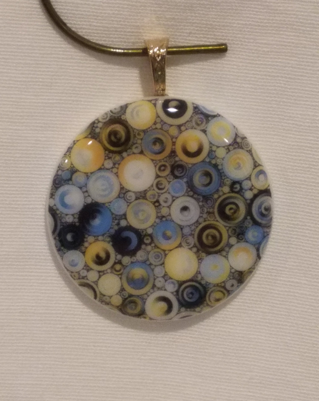 Blue & yellow bubbles float everywhere on a white background fused glass pendant