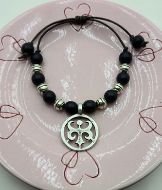 Wonderful casual attire leather slider bracelet silver pewter fleur-de-lis flanked black wood beads and silver plated ceramic beads.