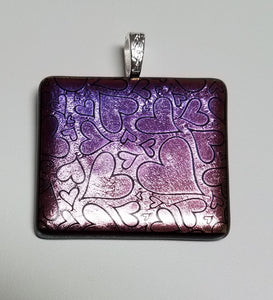 An elegant piece with hearts etched onto purple hues dichroic glass