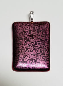 Black swirls are etched onto red dichroic glass