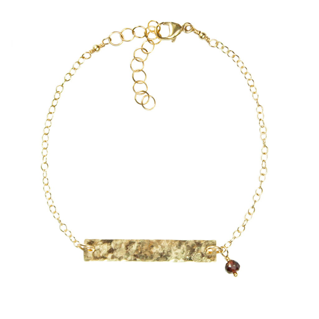 Gold bar bracelet with garnet accent