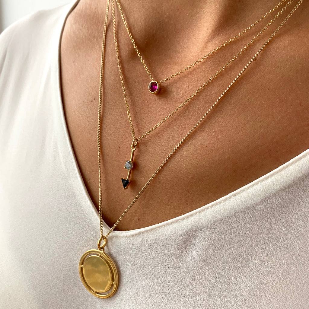 Medallion Pendant Necklace with cut-outs in gold on model, layered