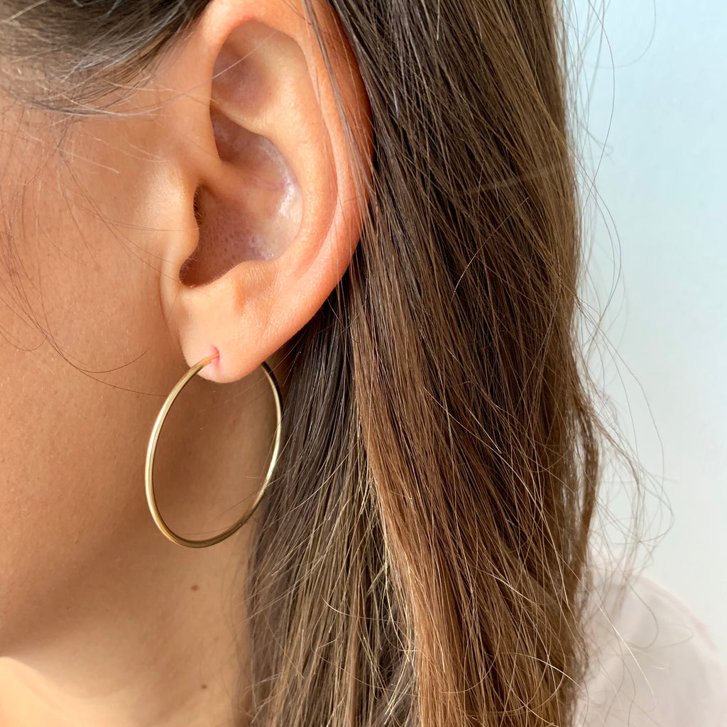 Mid-sized gold hoop earrings on model