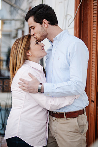 Man kissing his mother on forehead