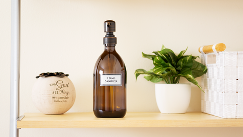 "Amber apothecary bottle with oil rubbed bronze pump and ""Hand Sanitizer"" printed."