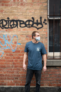 Man with mask in alley wearing covid 19 shirt by elk draws