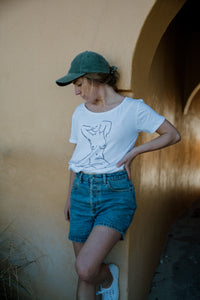 Girl standing in denim shorts wearing white organic cotton tshirt wth nude female form line art design on front by elk draws