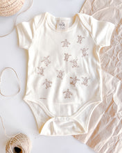 Load image into Gallery viewer, Baby ecru organic cotton onesie with turtle hatchlings on it.