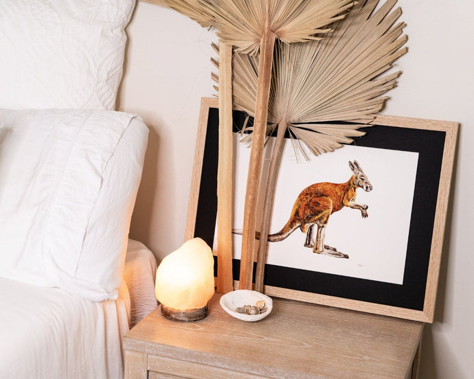 Kangaroo print on side table of white linen bed
