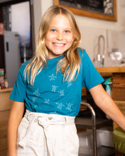 Load image into Gallery viewer, Young girl wearing blue organic cotton tshirt with turtle hatchlings on it.