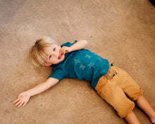 Load image into Gallery viewer, Young boy wearing blue organic cotton tshirt with turtle hatchlings on it.
