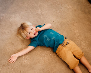 Young boy wearing blue organic cotton tshirt with turtle hatchlings on it.