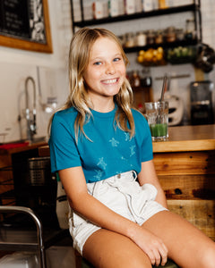 Young girl wearing blue organic cotton tshirt with turtle hatchlings on it.