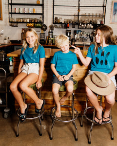 Three kids wearing elk draws organic cotton tshirts.