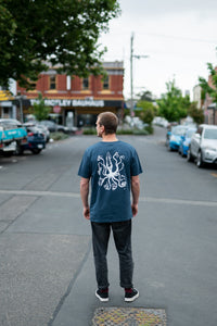 Man standing in city with blue organic cotton tshirt with covid squid design by elk draws
