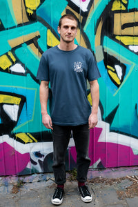 Man standing next to graffiti with blue organic cotton tshirt with covid squid design by elk draws