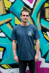 Man standing near graffiti with blue organic cotton tshirt with covid squid design by elk draws