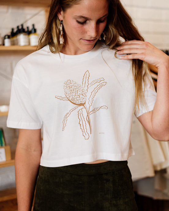 Female wearing elk draws white crop organic cotton tshirt with banksia on it.