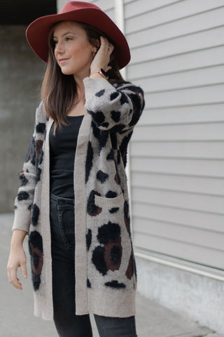 Girl wearing fuzzy leopard print cardigan and dark red fedora hat
