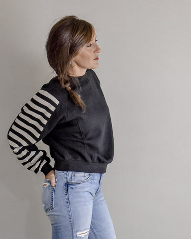 Girl wearing black mock neck sweatshirt with white stripes on sleeve
