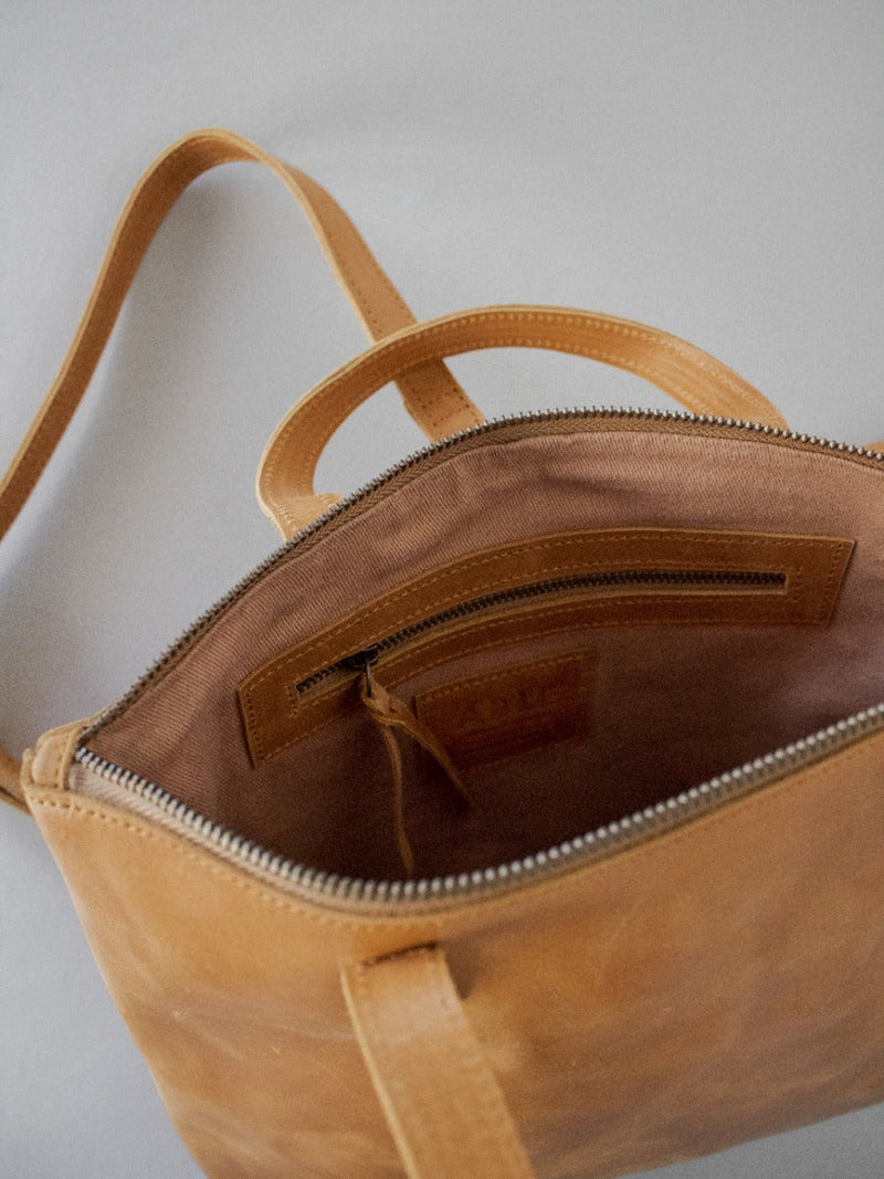 cognac leather backpack with interior zipper pocket and convertible straps
