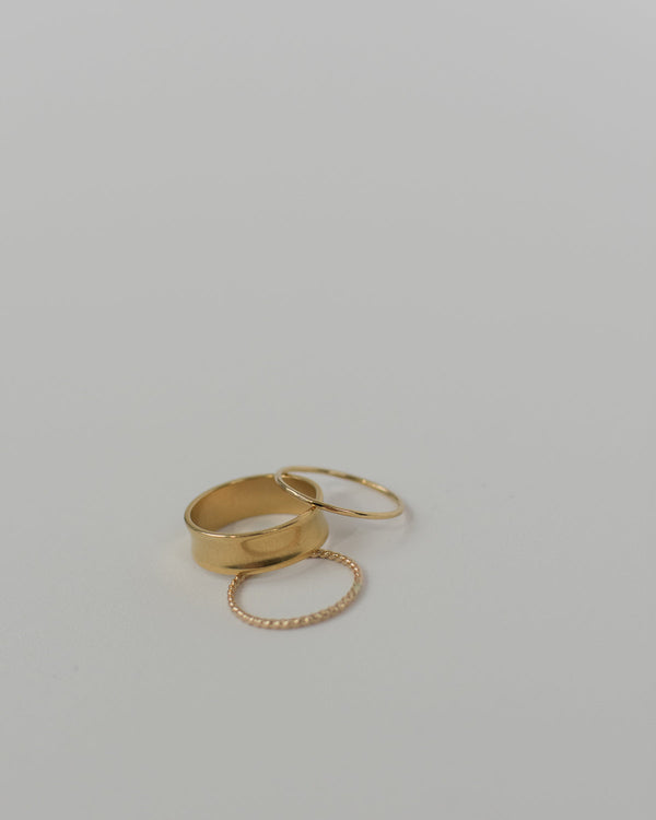 Three rings next to each other, one being the thick gold stacking ring, and two other thin gold rings.
