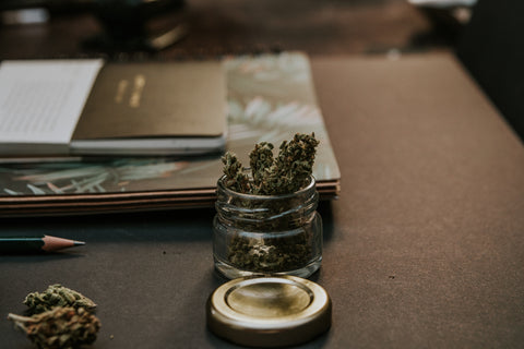 Jar of cannabis flower sitting on top of a wooden desk next to other office supplies, in an effort to compare THC vs. CBD