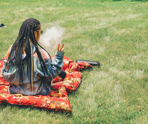 Girl smoking weed on a grassy lawn