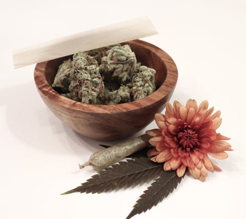 A pre-rolled 1 gram cannabis joint in front of a wooden bowl of large weed flower nugs with a pink flower in front of it all on top of a white table on 4/20