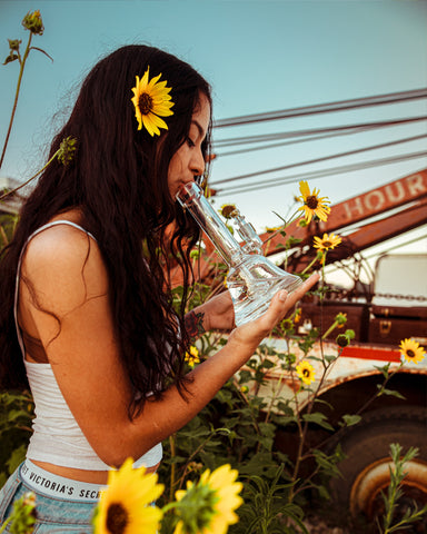Girl with dark hair and a sunflower in her hair and around her wearing a white tank top and blue jean shorts smoking a clear glass bong outside on a beautiful sunny 4/20 day