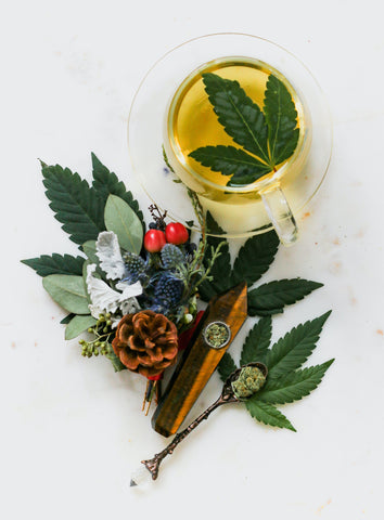 Wooden pipe on top of  cannabis fan leaves  in front of cannabis infused tea as a 4/20 gift in 2021