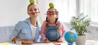 Little girl and her mom with pencils under nose and apple on their heads