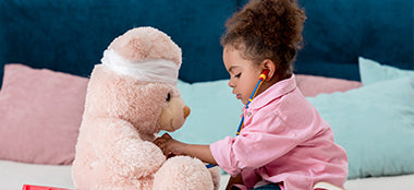 Little girl playing doctor with her teddy bear