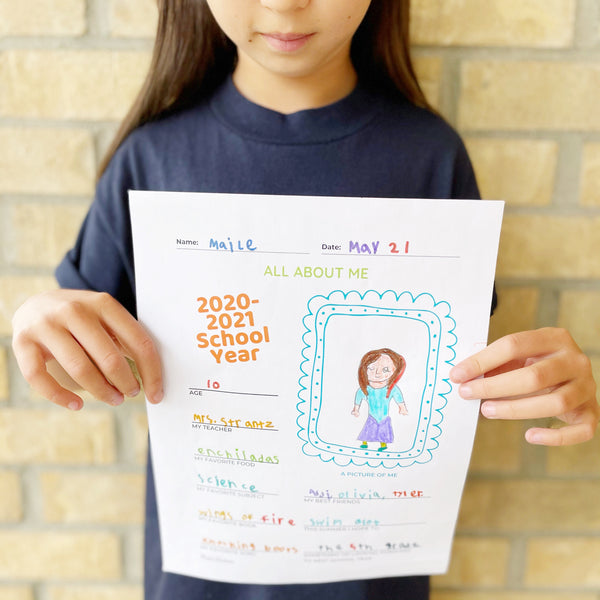 light colored brick wall background; girl holding her School Year in Review Printable for Kids with a self-portrait and colorful writing