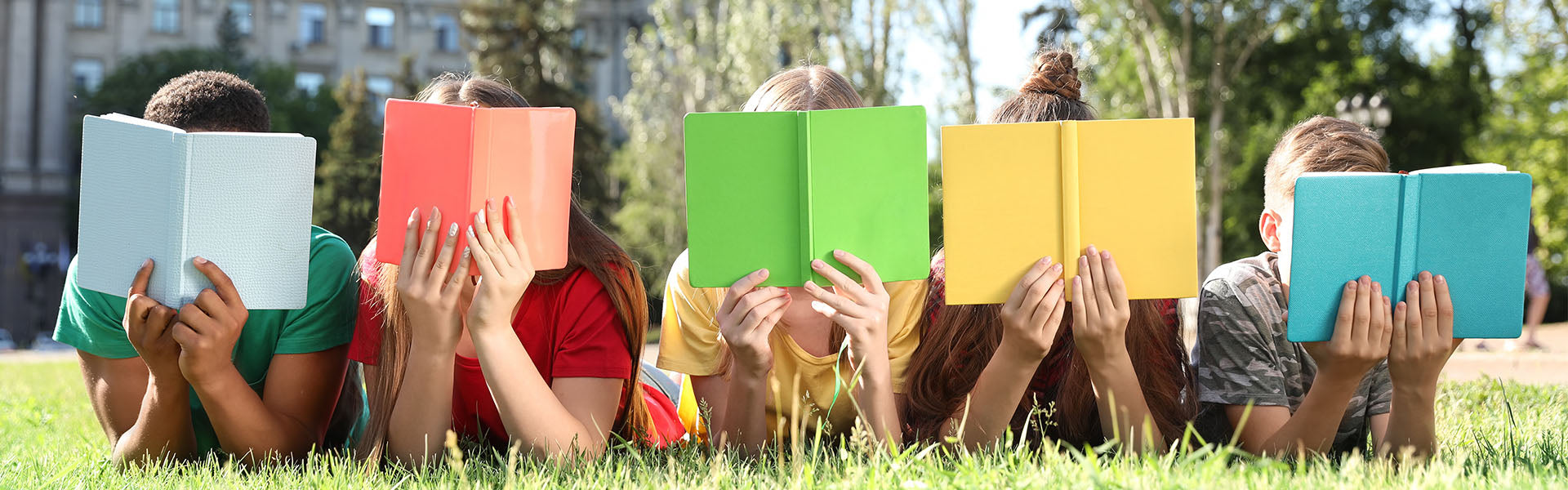 Kids reading in the grass during the summer