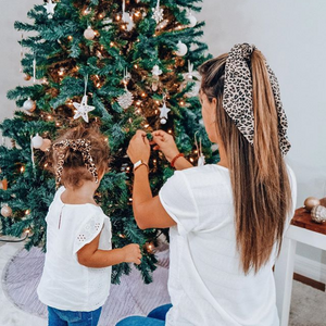 Mom and girl decorating tree