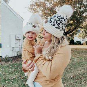Baby wearing leopard beanie with mom