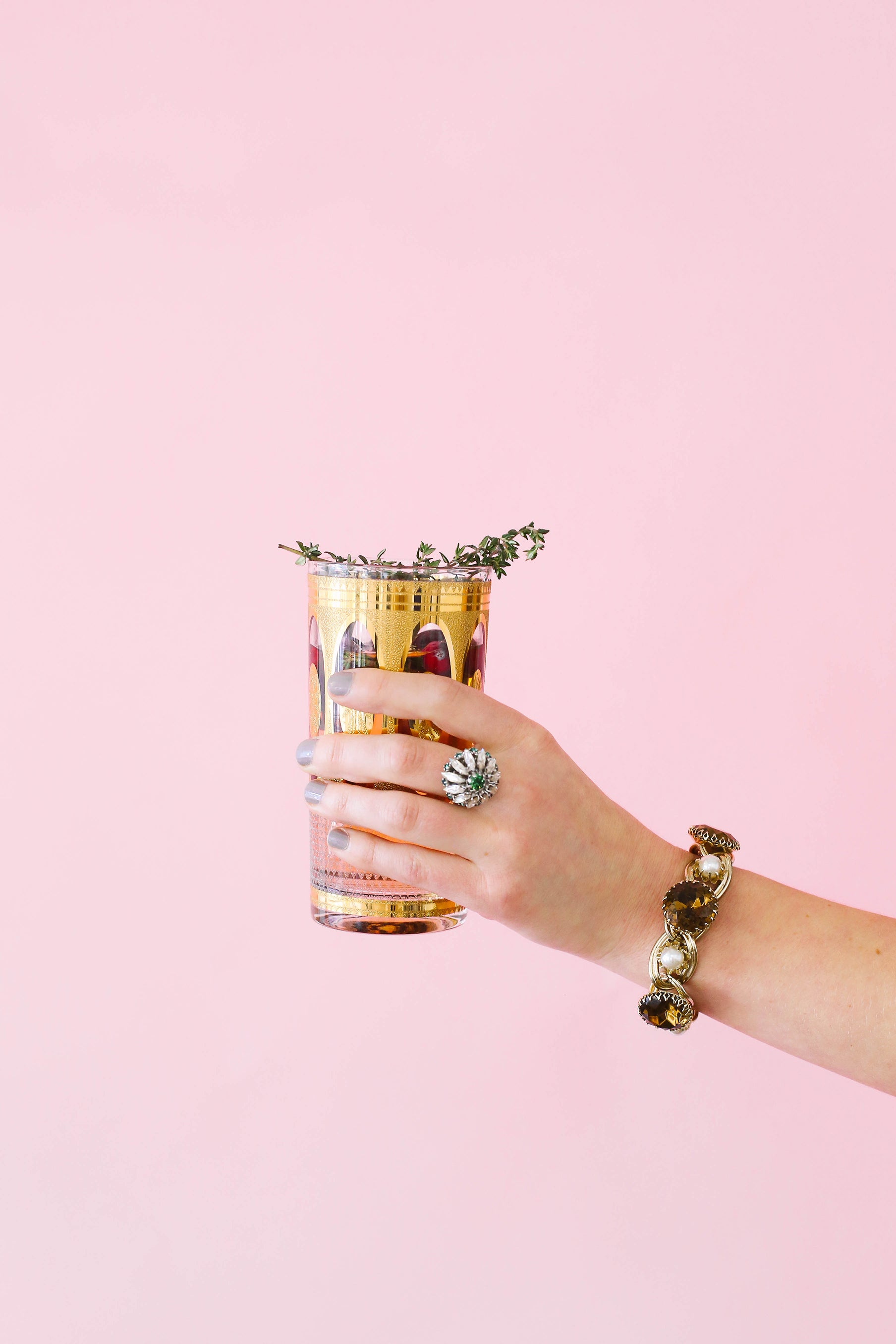 Vintage cocktail glass with statement bracelet and ring.