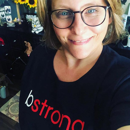 Woman with glasses wearing a bstrong shirt for Bethenny Frankel's charity