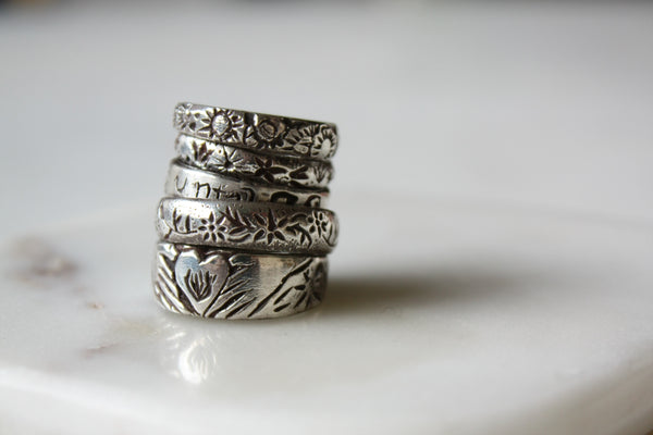 stack of 5 silver bands with floral designs, with secret messages engraved on the inside, also known as poesy rings