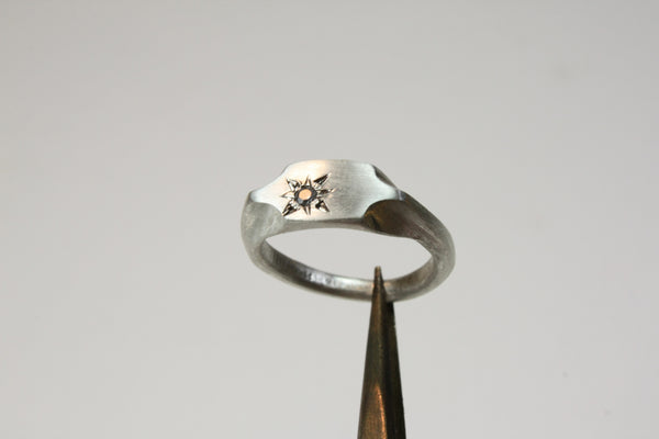 signet ring with single sapphire stone, held by tweezers
