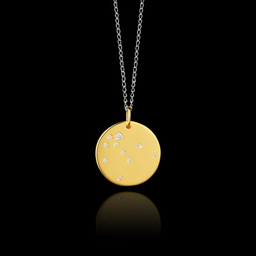 Close up of Aquarius Zodiac star sign pendant in gold with silver chain. Made by British jewellery designer Catherine Zoraida