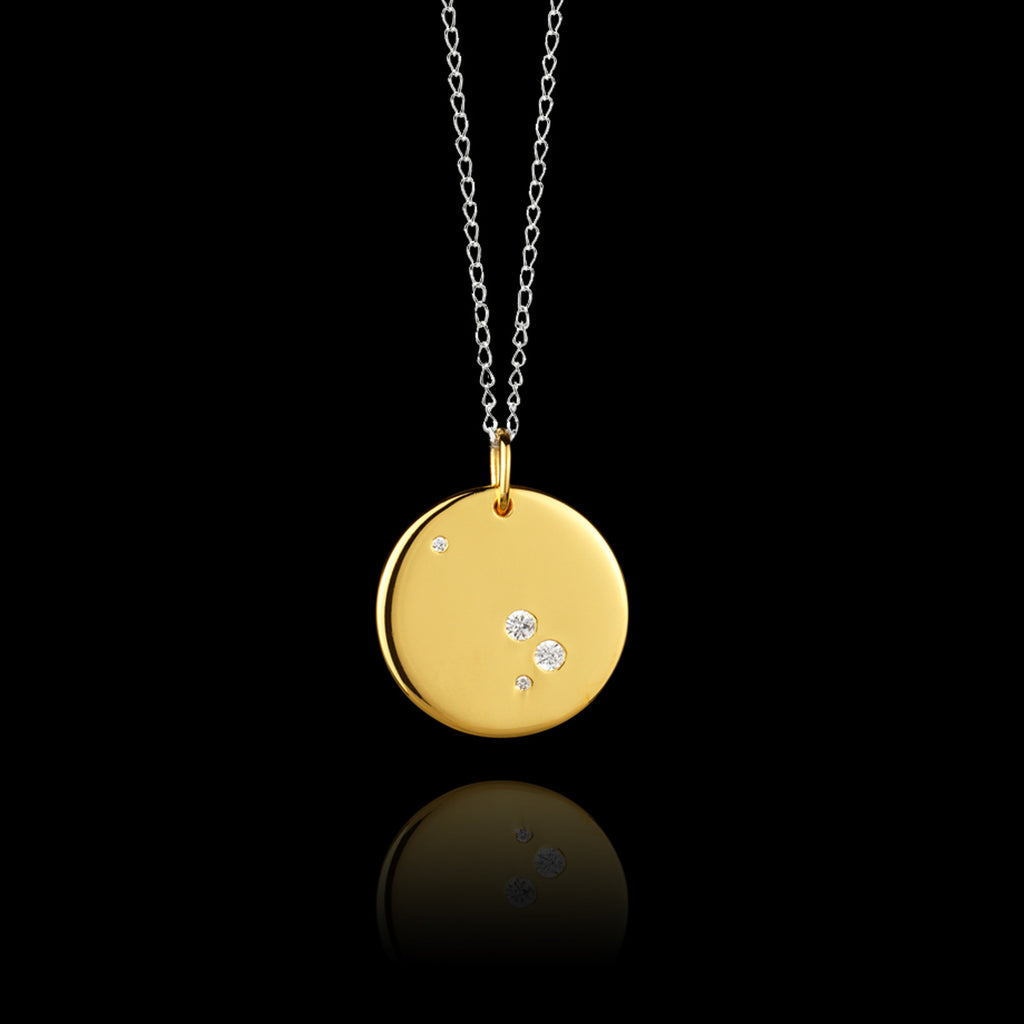 Close up of Aries Zodiac star sign pendant in gold with silver chain. Made by British jewellery designer Catherine Zoraida
