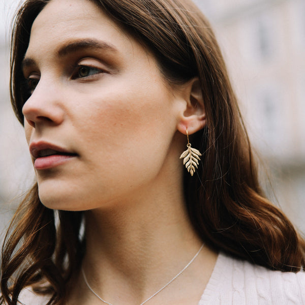 Model wears Catherine Zoraida Gold Fern Drop Earrings